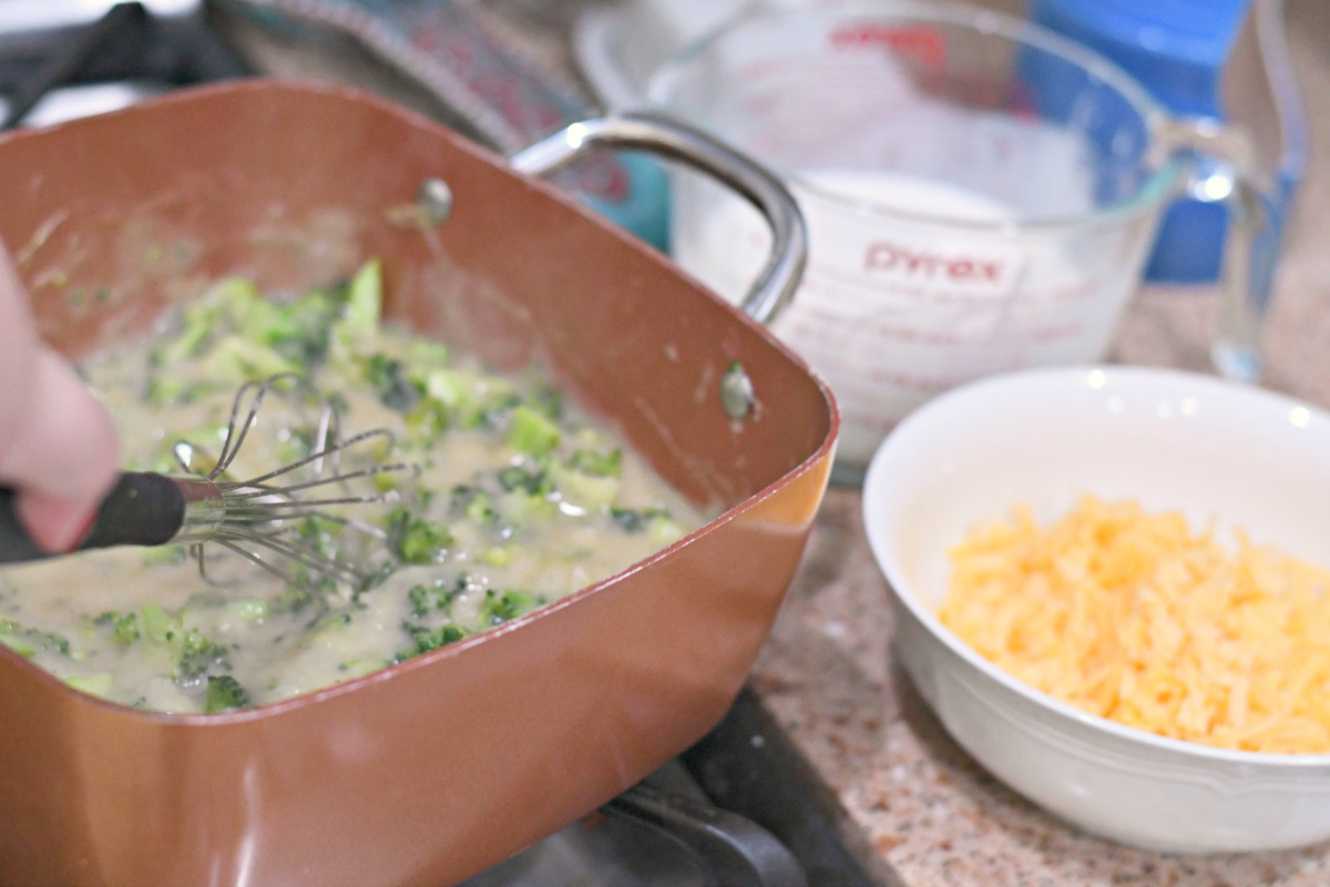 broccoli cheddar cobbler ingredients being cooked on the stove