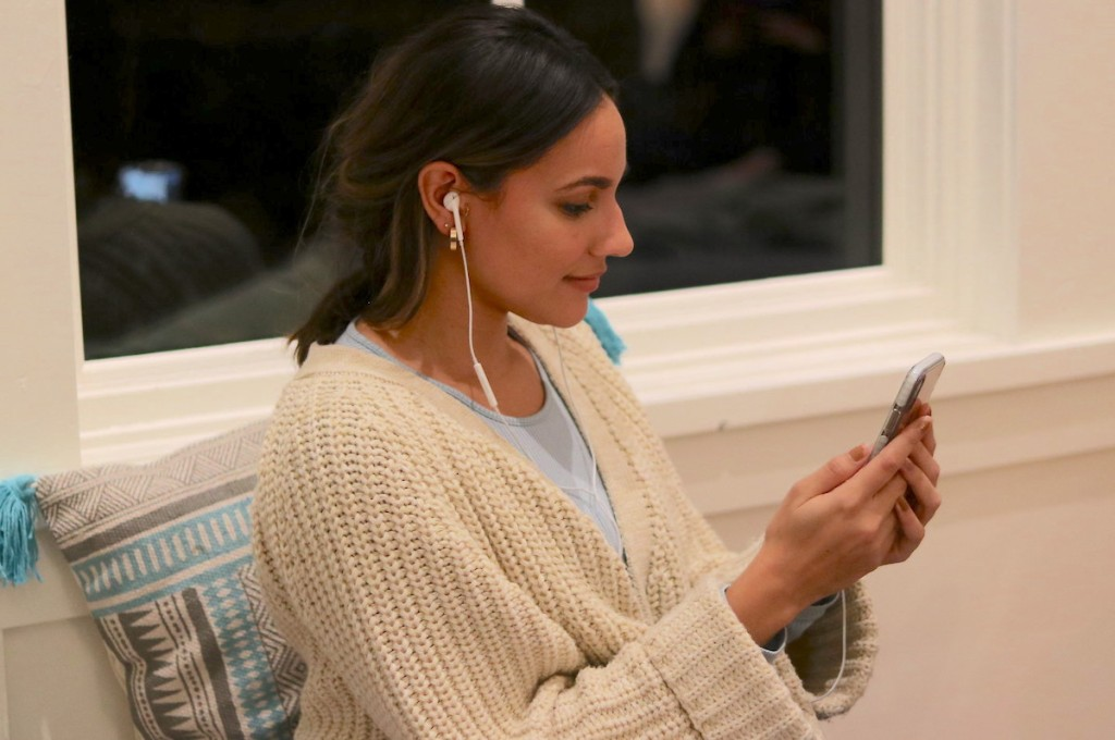 woman wearing headphone looking at cell phone