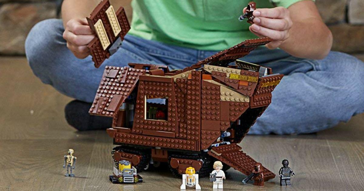 boy playing with LEGO Sandcrawler set