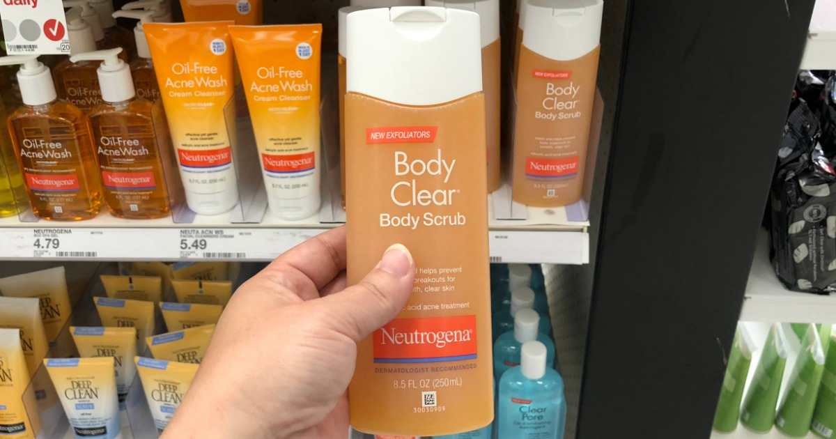 hand holding a bottle of neutrogena body scrub in front of a store display