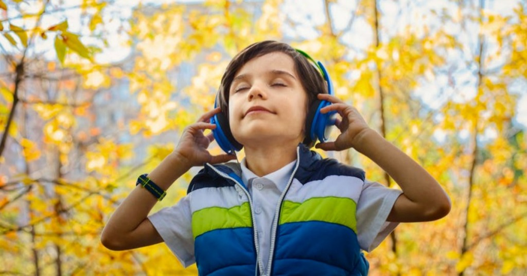 boy listening to music in the woods