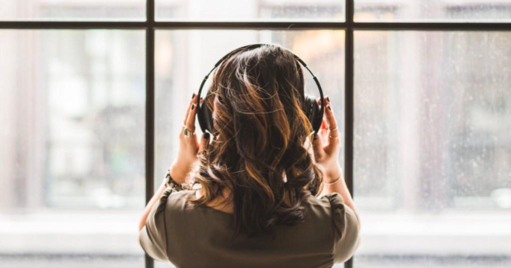 woman listening to headphones standing in front of window