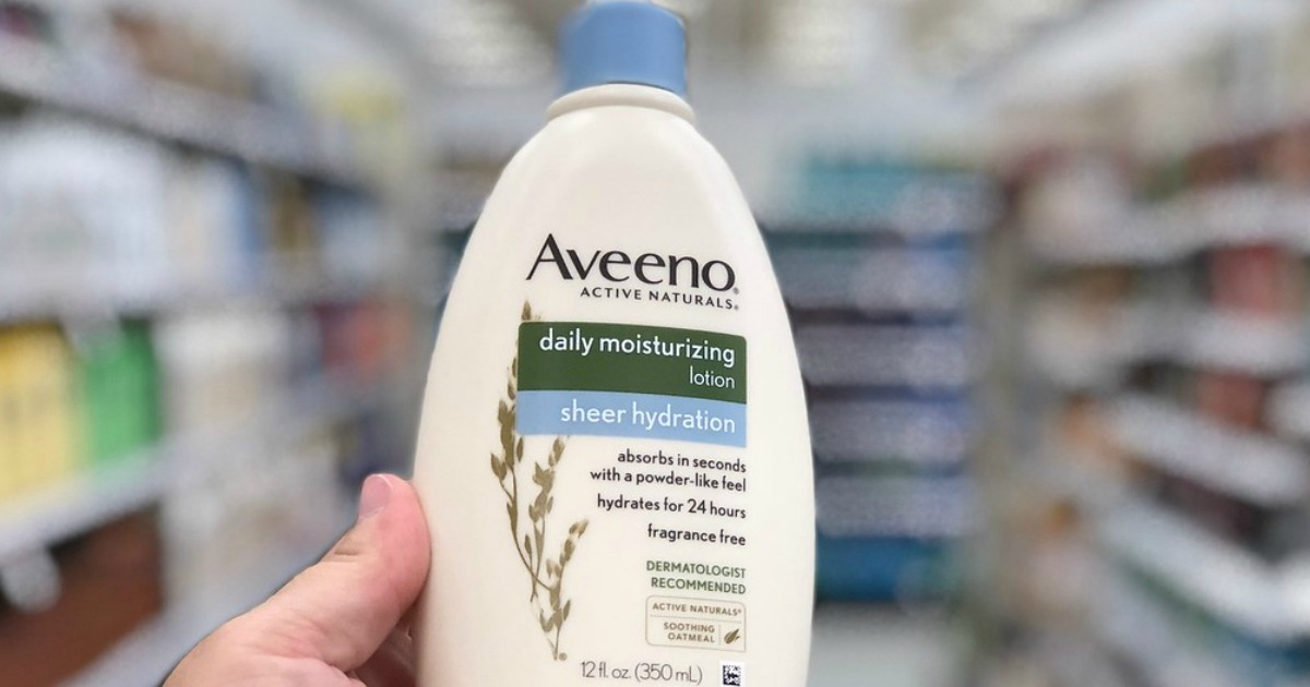 hand holding aveeno daily moisturizing lotion and blurry background