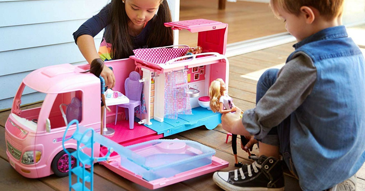 Girl and boy playing with Barbie DreamCamper