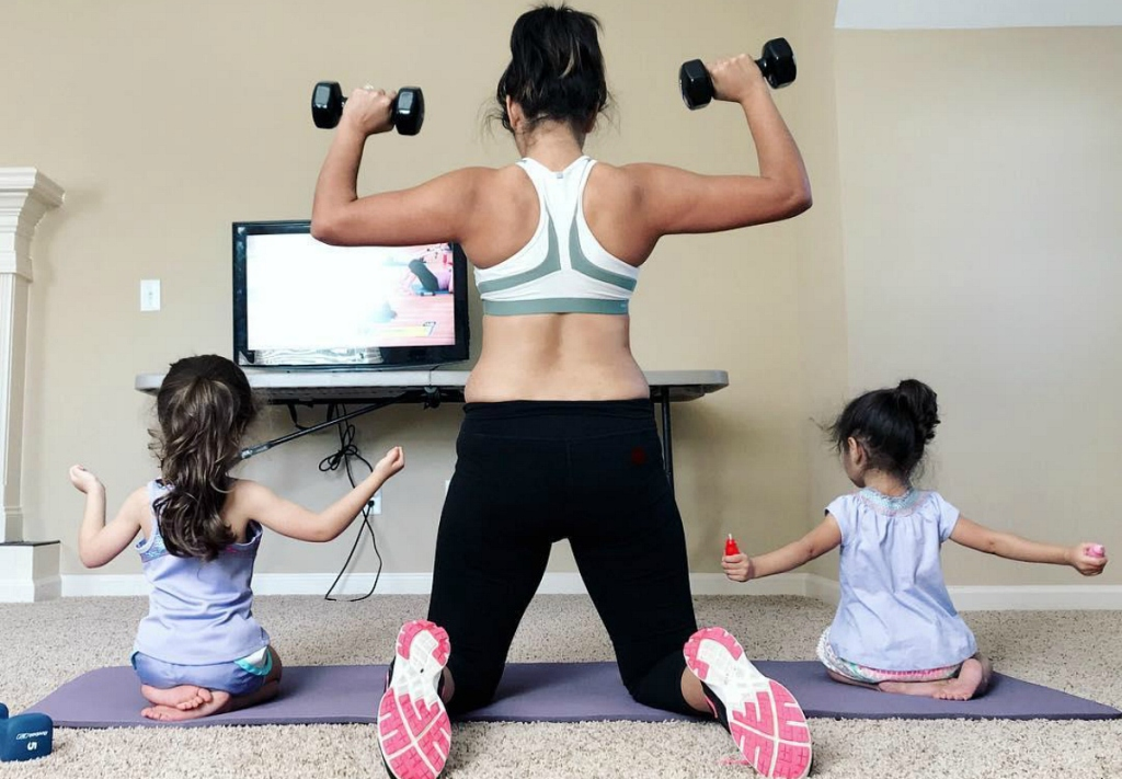 woman lifting weights with kids on either side