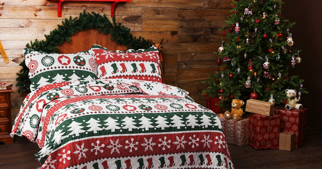 christmas quilt on bed in bedroom with christmas tree in corner