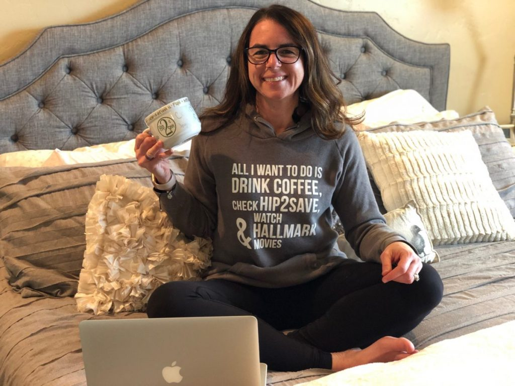 woman sitting on bed with sweatshirt holding coffee cup