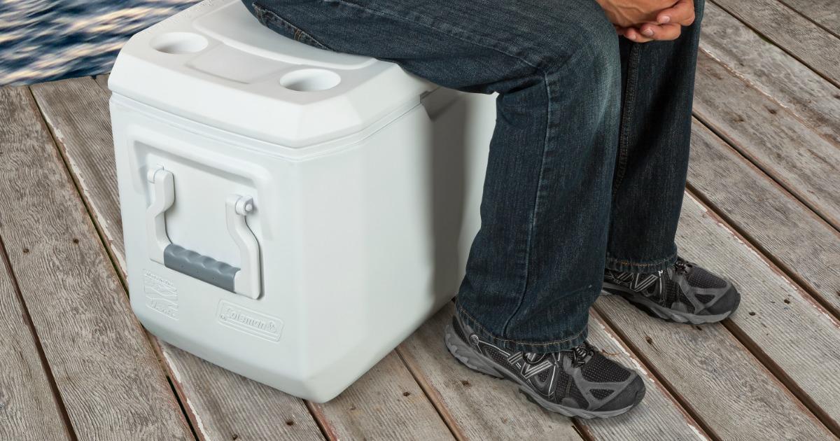 man sitting on Coleman cooler
