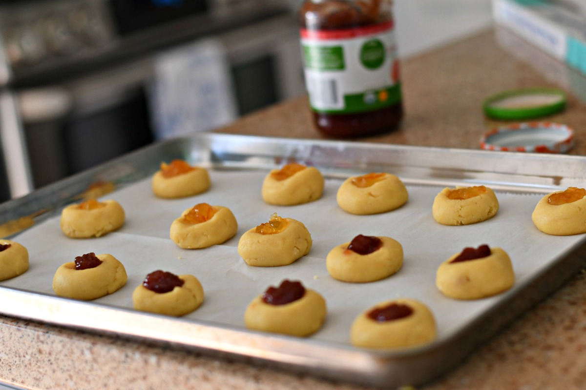 cookie dough christmas cookies recipe – thumbprint jam cookies on a tray prior to cooking