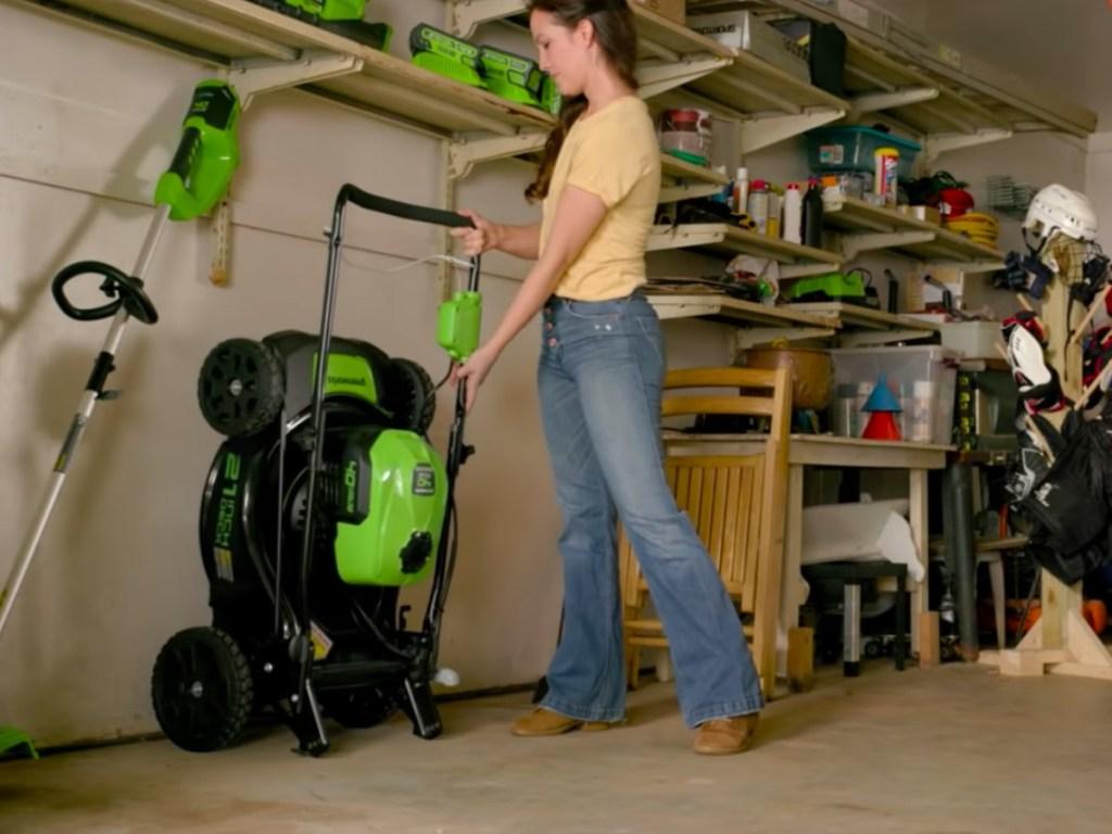 Greenworks Brushless Cordless Mower being folded up in garage