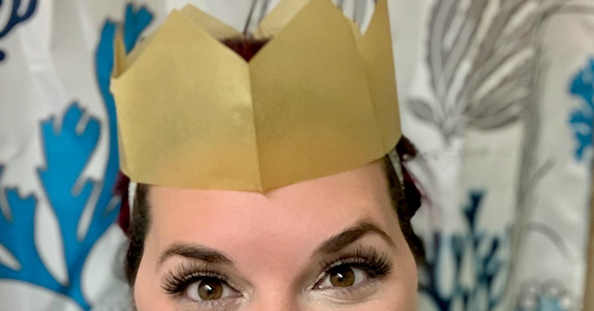 woman wearing gold paper crown and fake eyelashes