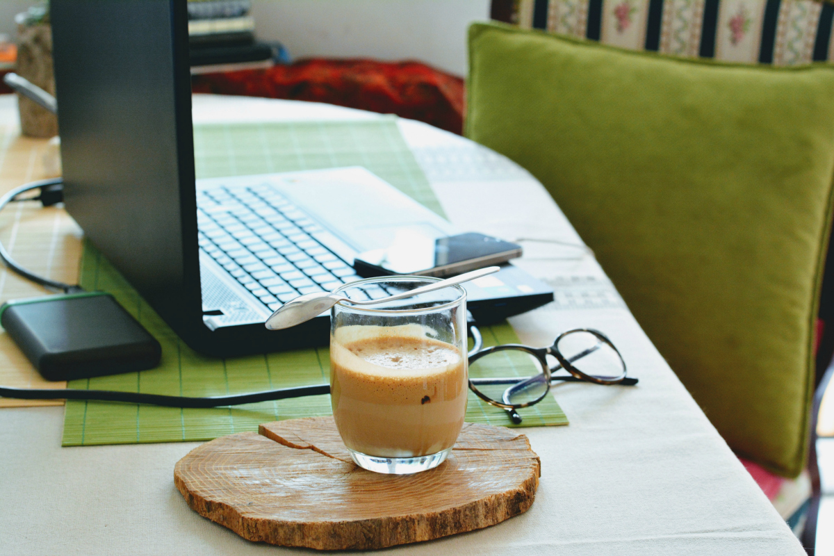 a cup of coffee next to an open laptop