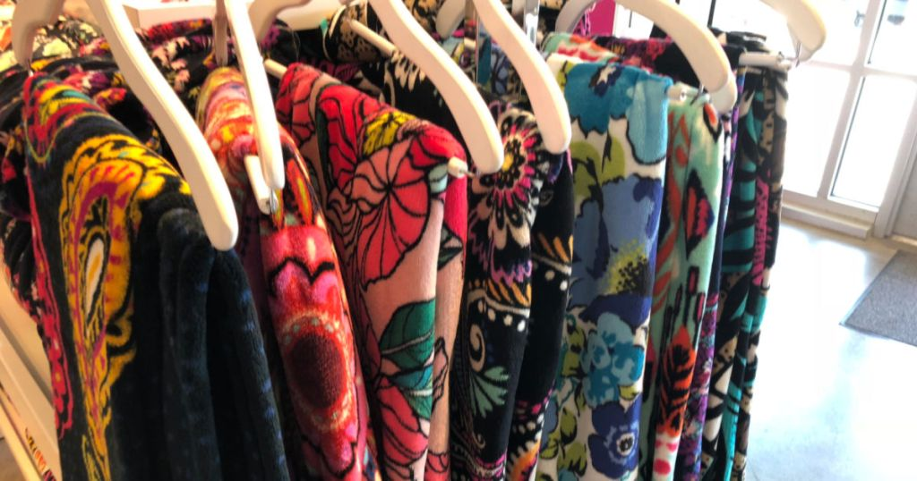 vera bradley throw blankets on hangers in store