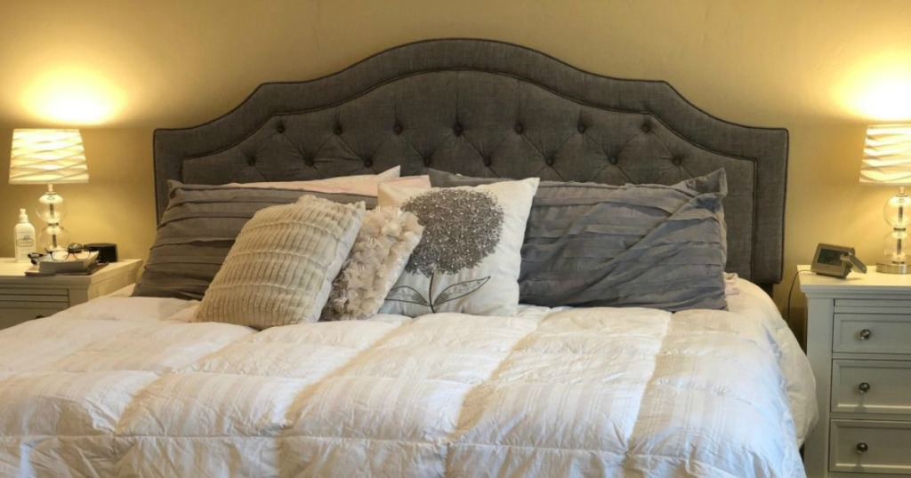 bedroom with gray headboard and numerous pillows