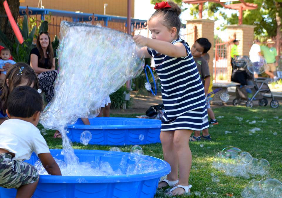 girl playing outside with bubbles