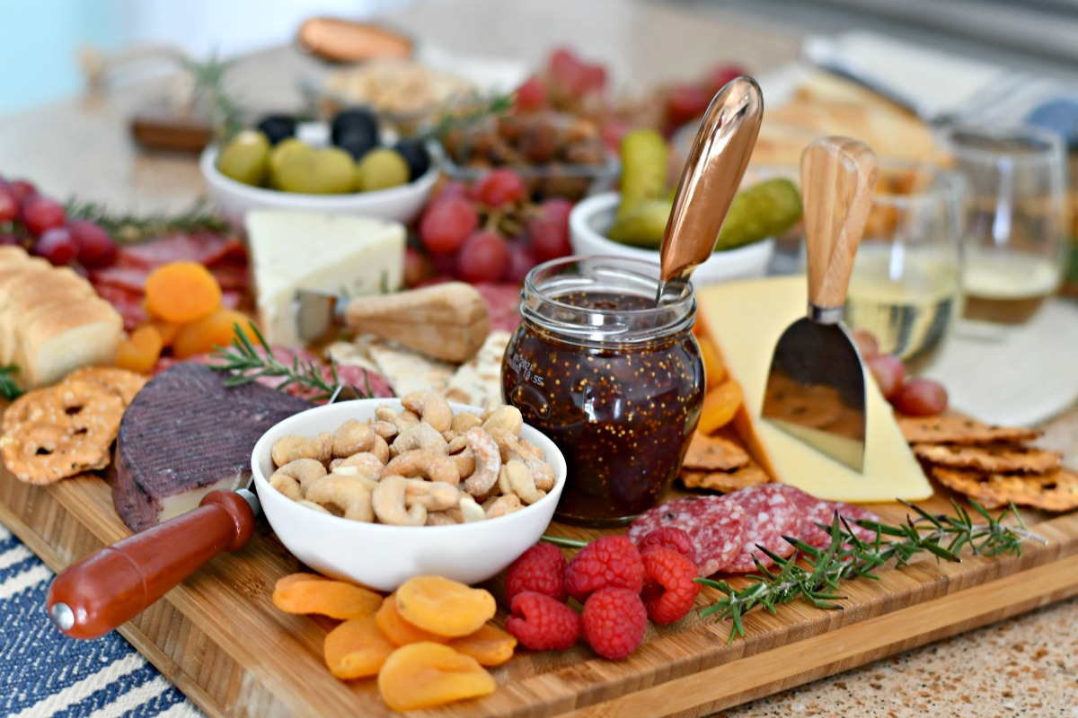 nuts, dried fruit, jam, cheese, olives on cutting board