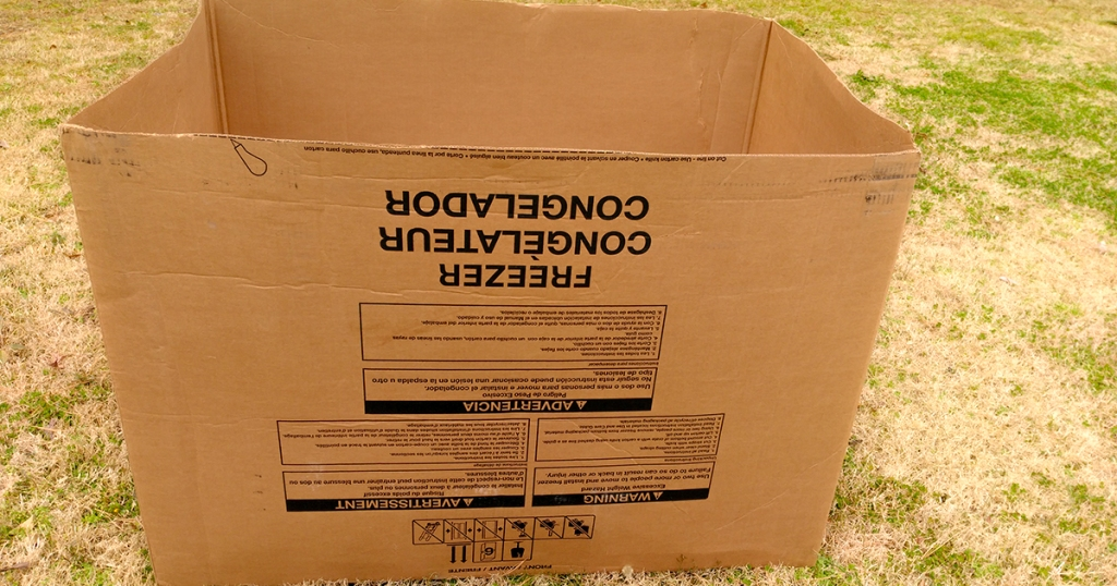 empty cardboard freezer box on lawn
