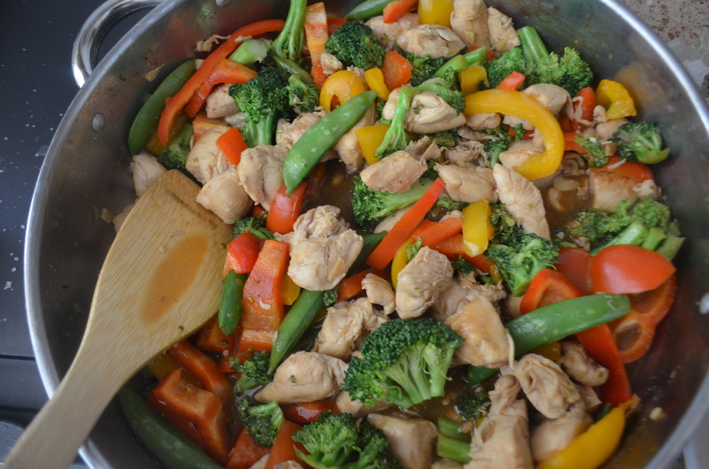 chicken stir fry with broccoli and bell peppers in pan with wood spoon