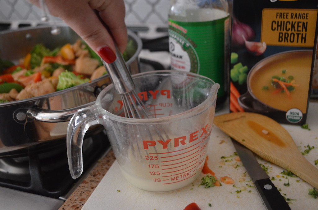pan with chicken stir fry and mixing sauce in pyrex glass measuring cup