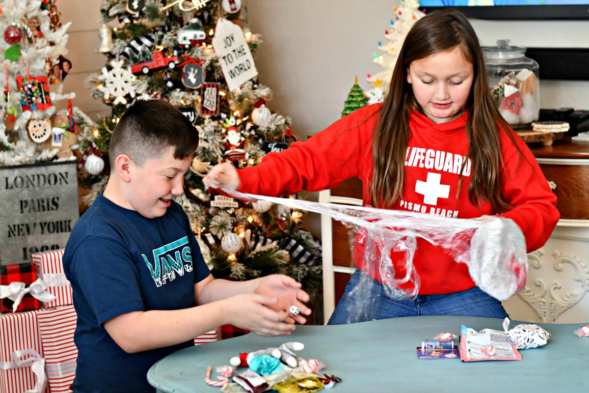 Saran wrap game holiday party game – kids wrapping gifts in Saran Wrap