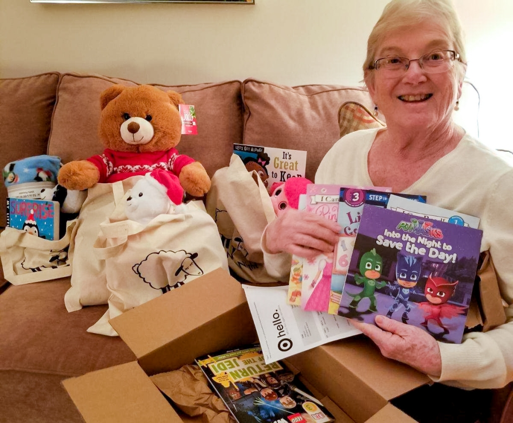 reader giving back — dee holding up books from target for donation to project night night
