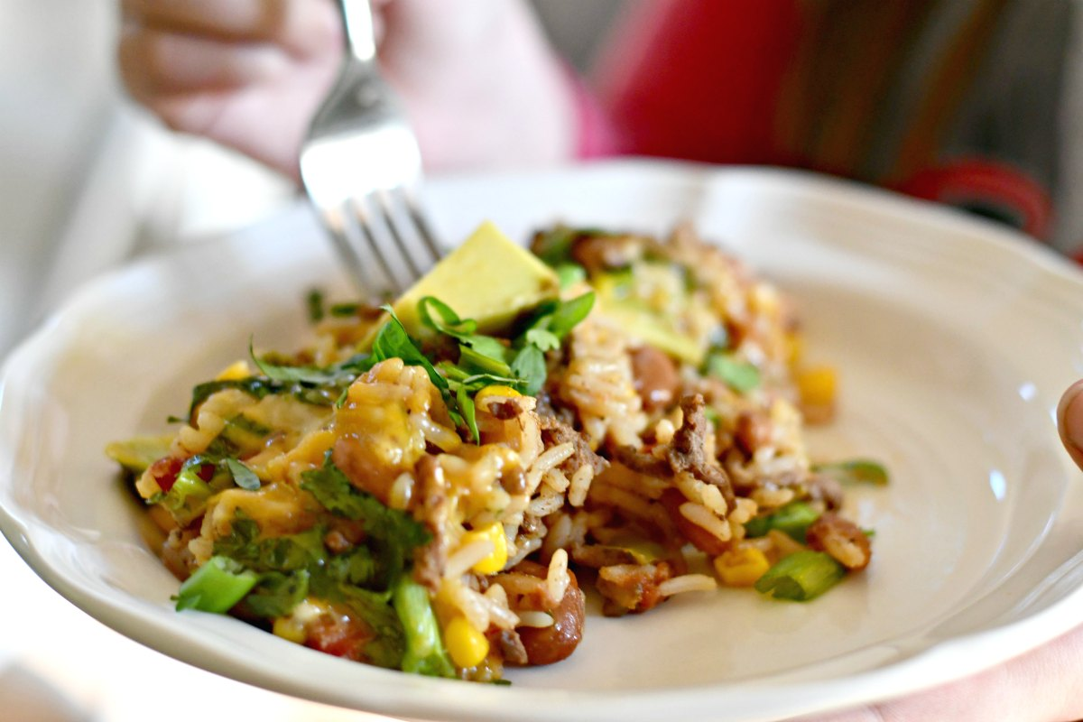 taco rice beans skillet casserole – a fork going into a plate of the casserole