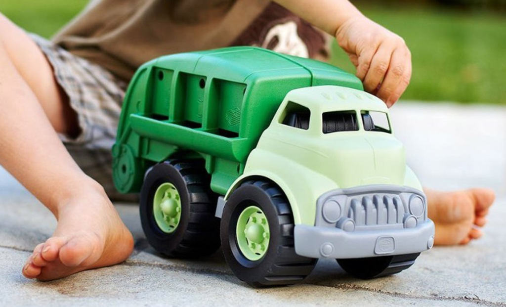 small child playing with green toys green truck