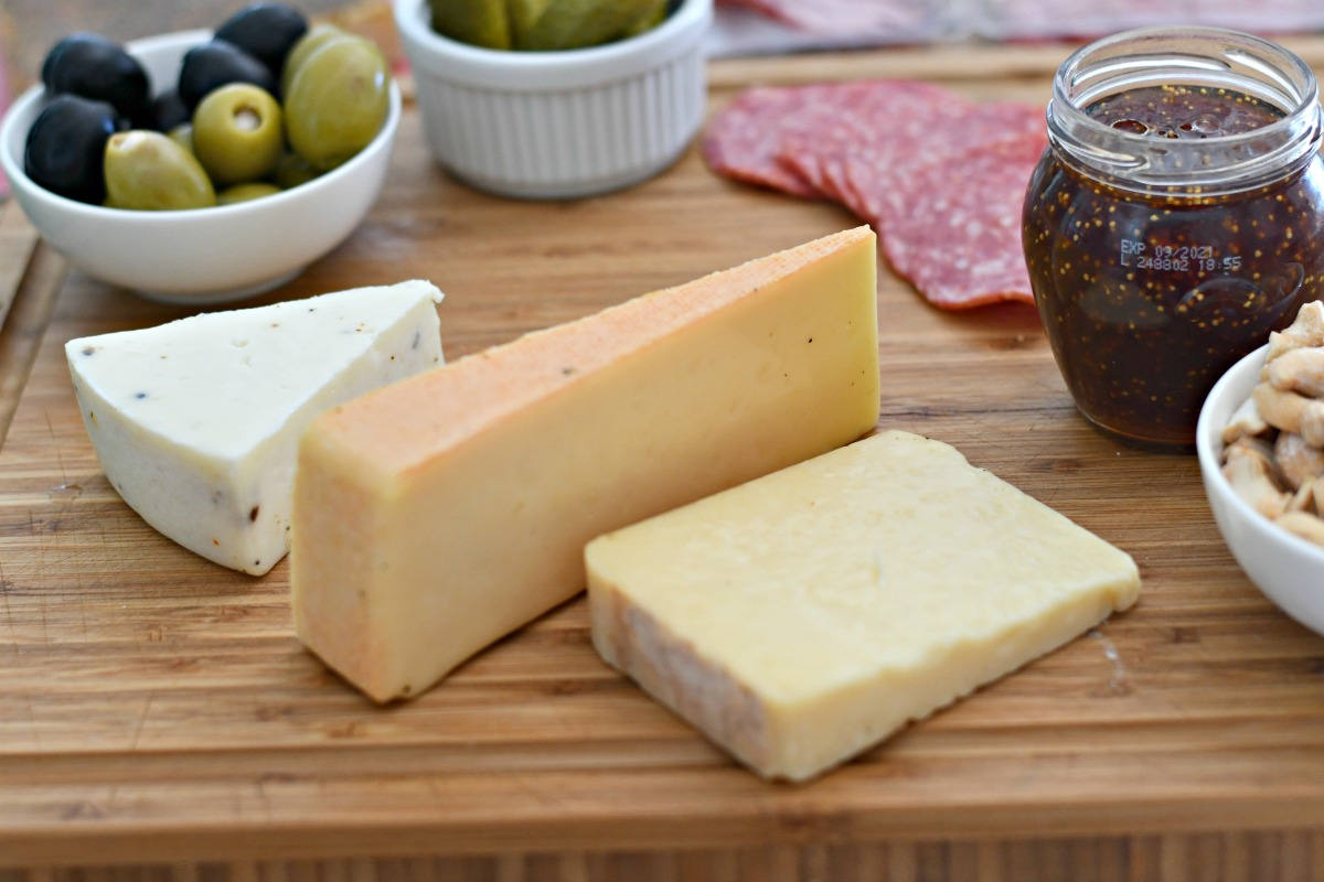 cheese, olives, jam, and meat on wooden cutting board