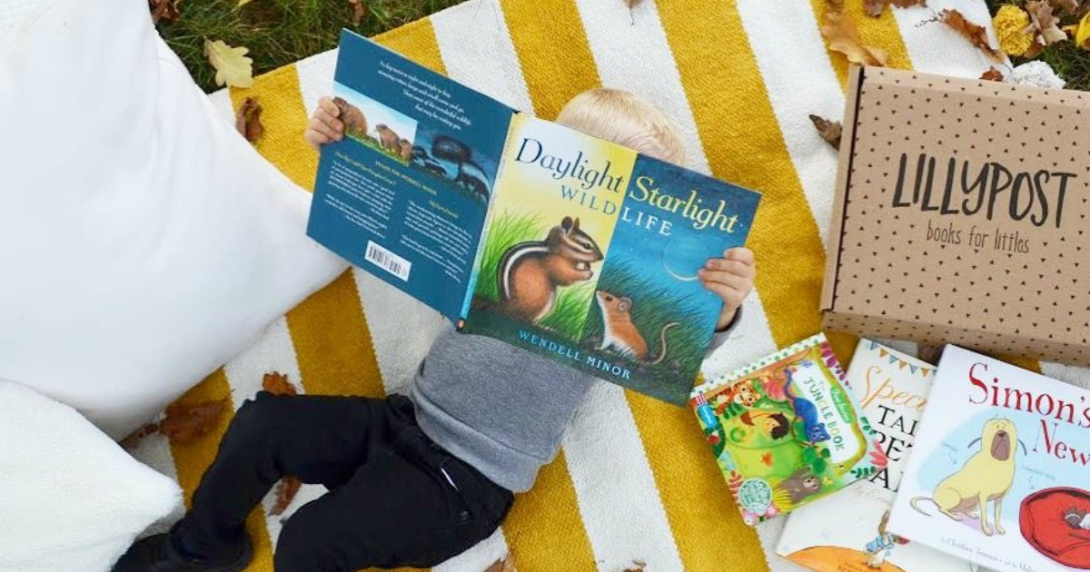 lillypost kids books subscription box promo code deal – young boy reading a book on a blanket outside
