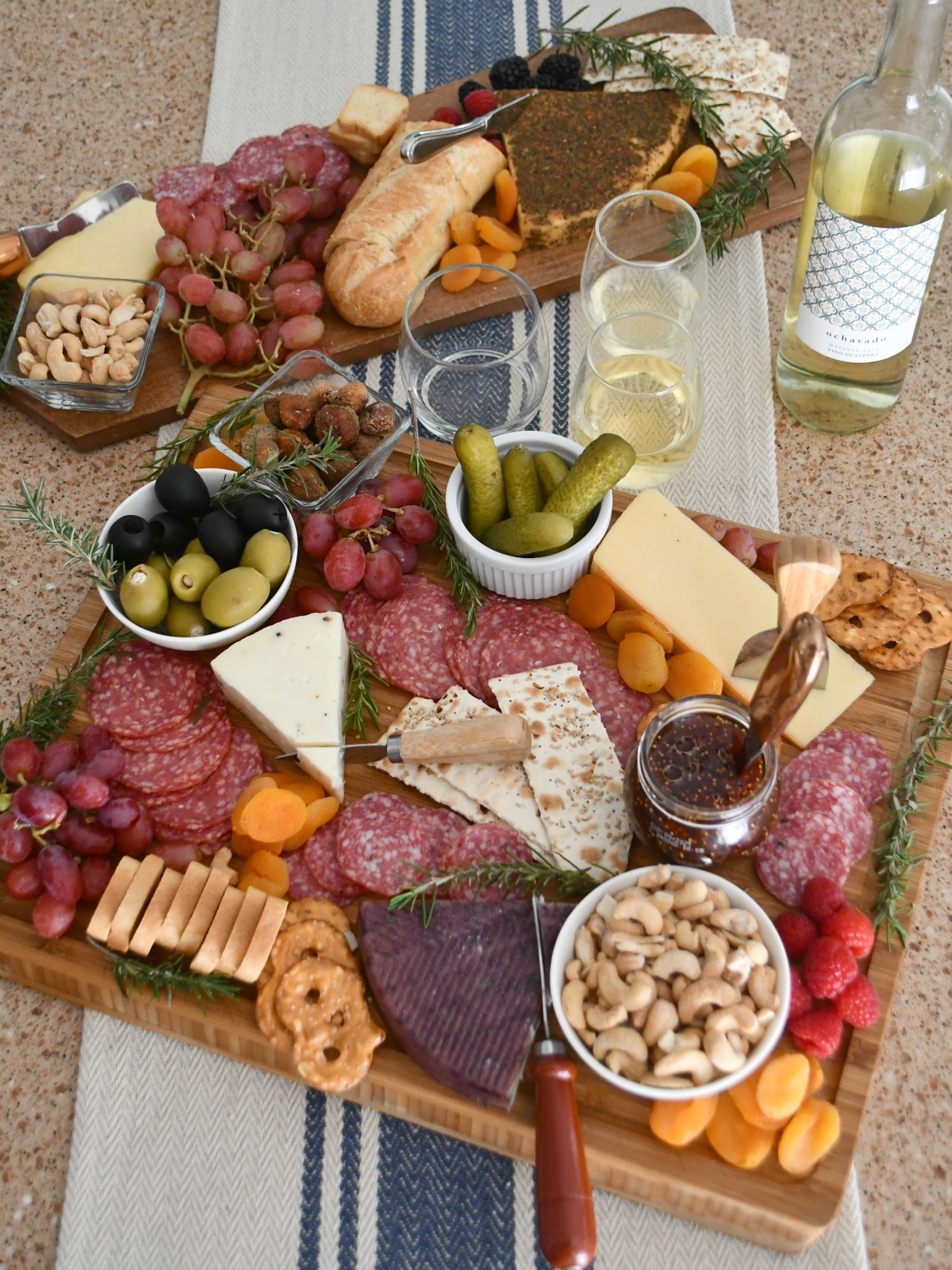 charcuterie boards with cheese assortment, wine, a bread loaf, glasses, and more