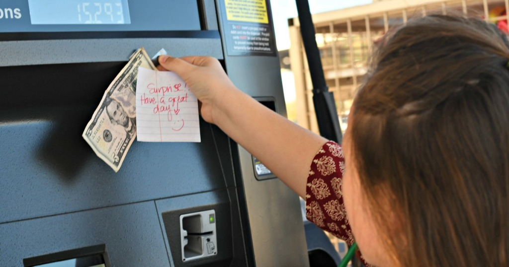 girl taping money to a gas tank