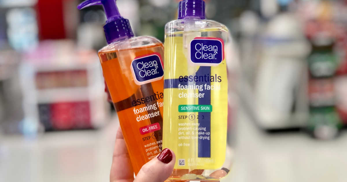 womans hand holding two bottles of clean and clear face washes