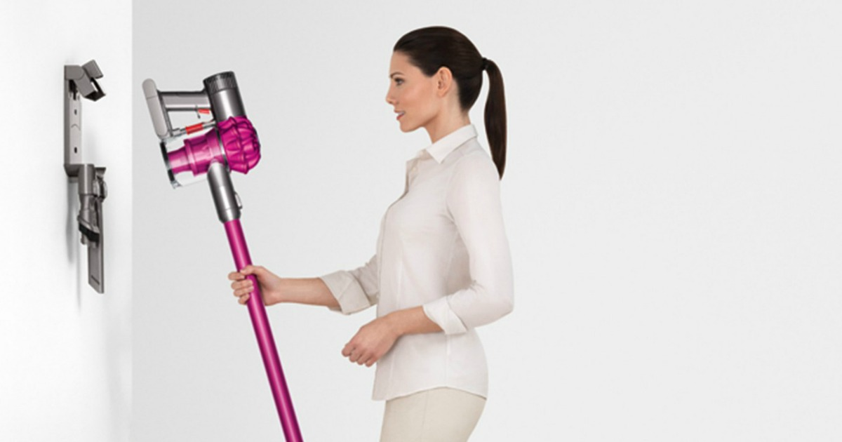 Dyson V6 Cord Free Vacuum with woman plugging it in to charge on wall charger