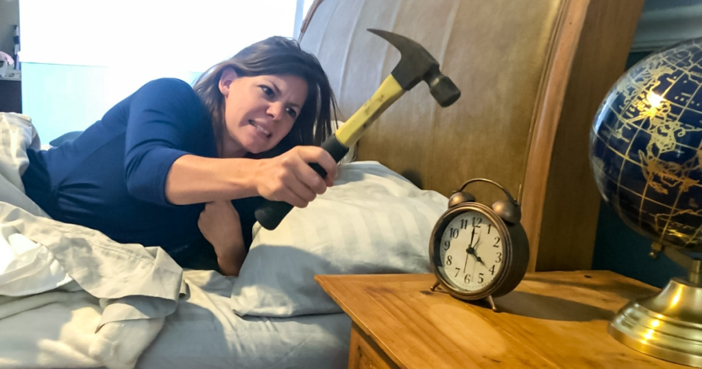 erica using a hammer to hit an alarm clock