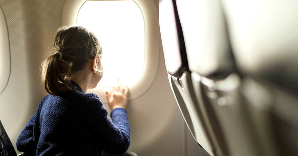Frontier Airlines offering free flights - child looking out plane window