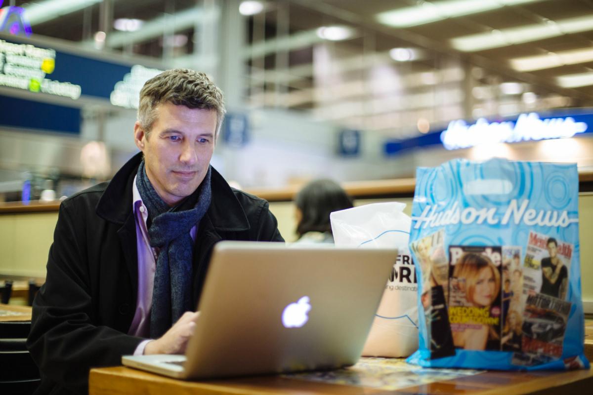 Hudson News man using a laptop