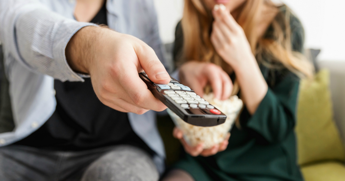 Man and woman watching television, with man holding the remote