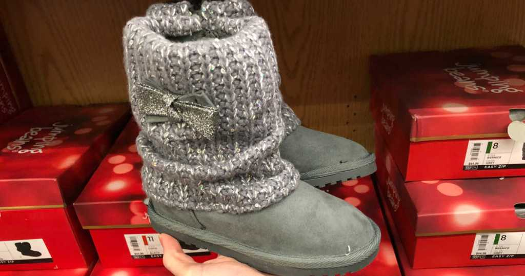 Woman hand holding grey Jumping Beans Odessa Toddler Girls' Sweater Boots in front of shoe boxes at store