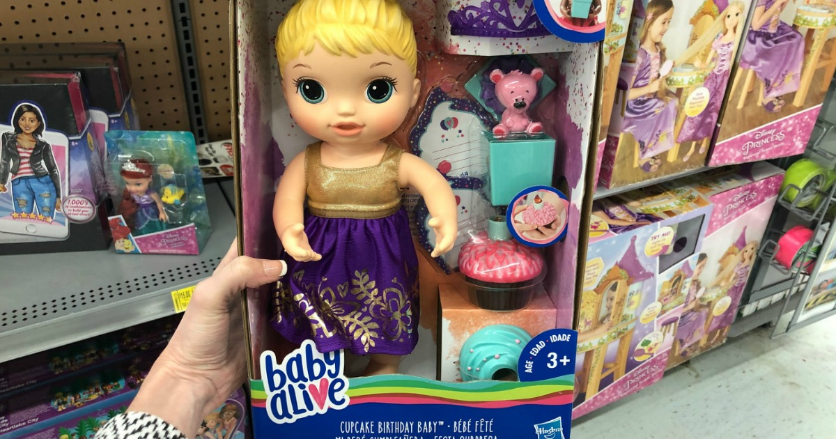woman holding baby alive doll in a box in-store