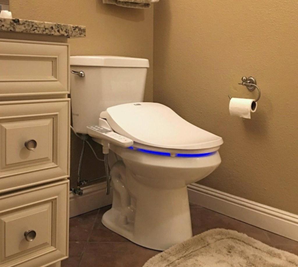 white toilet in bathroom next to vanity sink