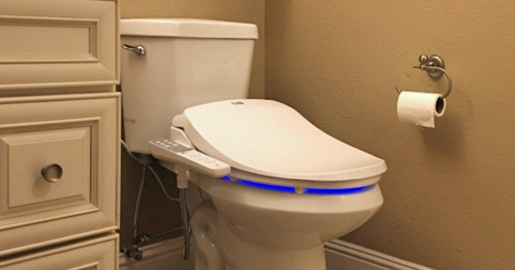 white toilet with bidet seat on top in bathroom