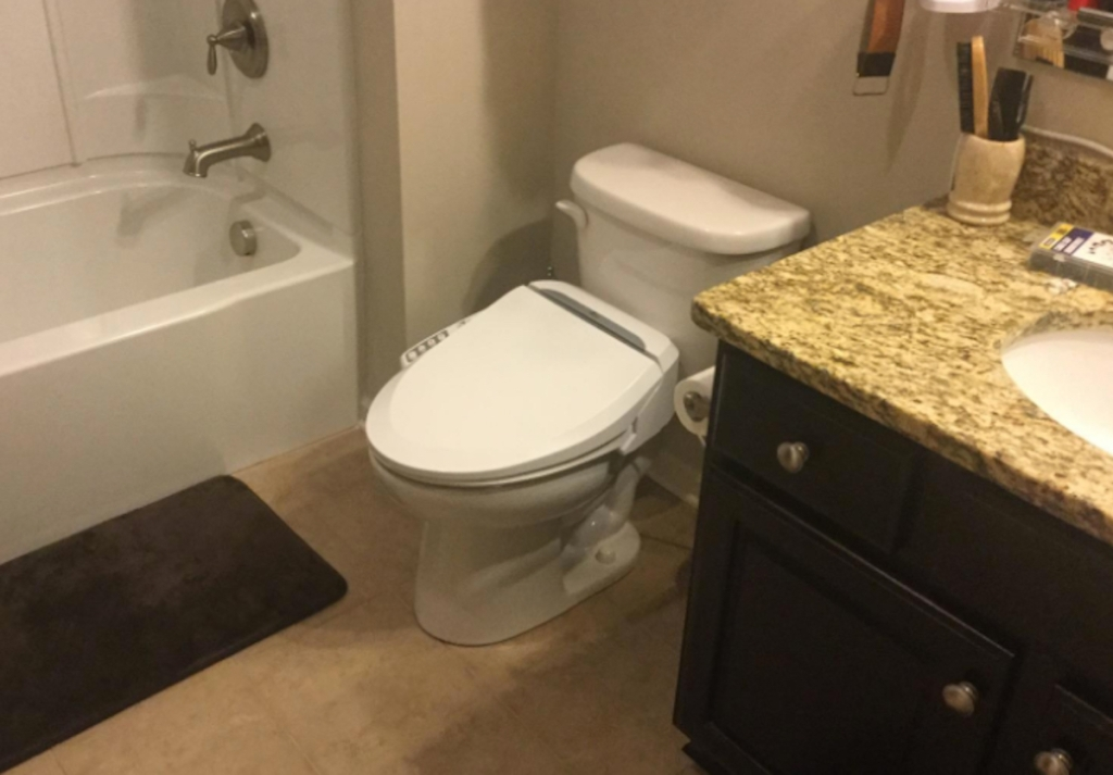 white toilet and sink in bathroom next to shower
