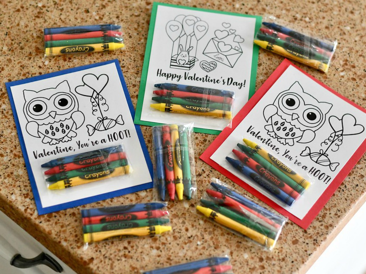 DIY Crayon Valentines (Free Printable Included) – completed Valentines on the counter with extra crayons
