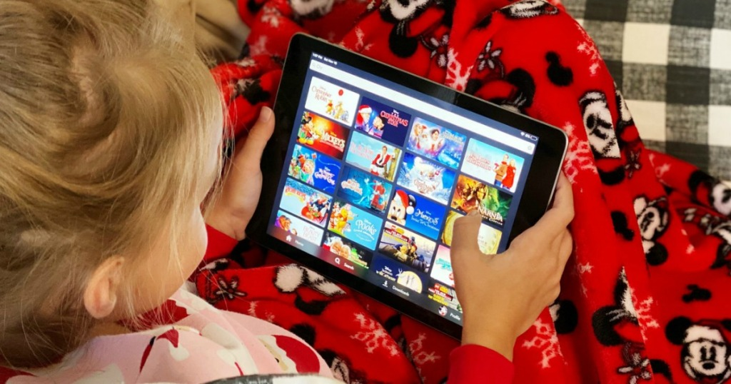 little girl on iPad using the Disney+ app with movies