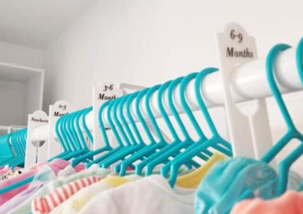 bright white closet with dividers and clothes hanging on blue hangers