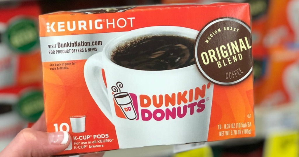 hand holding keurig hot dunkin donuts in store with blurry background