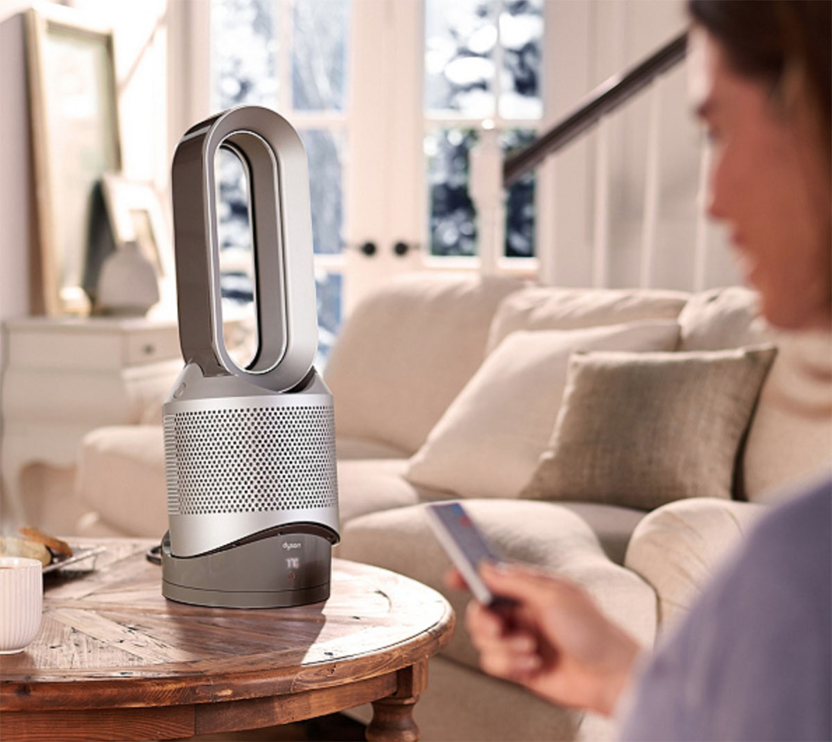 person using a remote to the dyson pure hot & cool fan