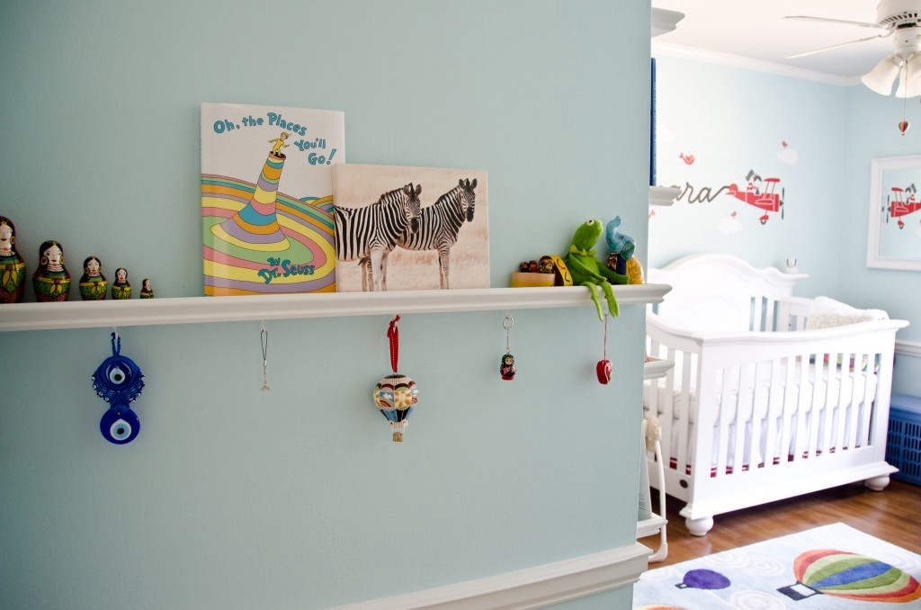floating shelf in nursery with books and decor