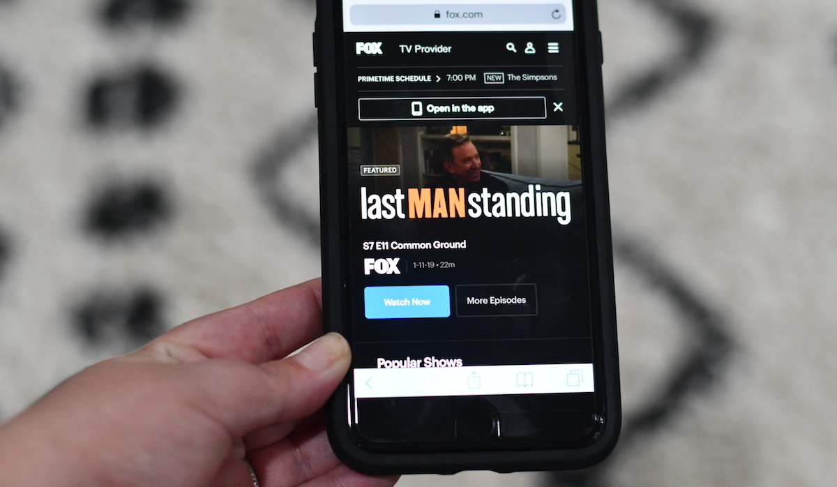 watch tv, movies, and sports for cheap or free – fox mobile app last man standing on phone screen