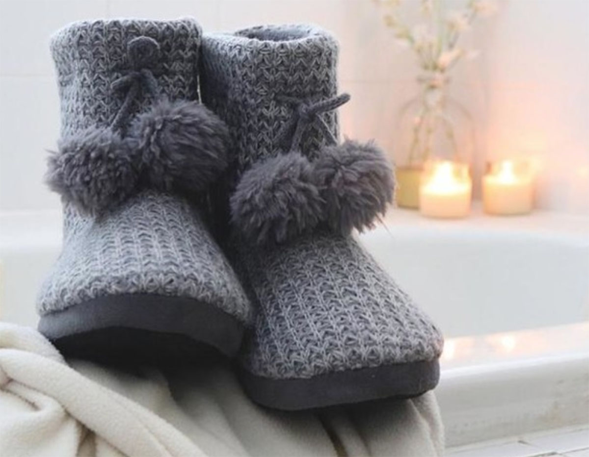 grey Isotoner slippers on a fuzzy blanket
